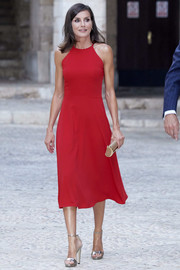 Queen Letizia added more shine with a gold tube clutch by Carolina Herrera.
