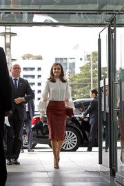 Queen Letizia of Spain paired a red leather pencil skirt by Hugo Boss with a white lace-panel blouse for a meeting in Seoul, South Korea.