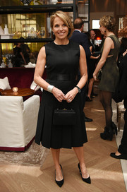 Katie Couric chose an elegant black satin purse to complement her dress.