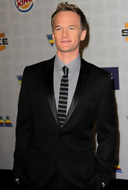 Neil looks sleek in a slick black suit with a thin satin lapel.
