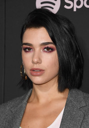 Dua Lipa highlighted her eyes with a smoky application of ruby shadow.