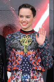 Daisy Ridley rocked a braided updo that she paired with natural makeup and a bright orange lip at the 'Star Wars: The Force Awakens' press event.