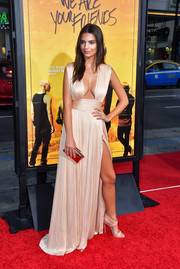 Emily Ratajkowski perfected her look with a metallic gold clutch by Treesje.