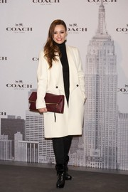Natalia Verbeke accessorized with an oversized maroon clutch for a bit of color.