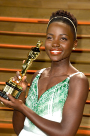 Lupita Nyong'o's bright orange lipstick contrasted nicely with her green dress during the Vanity Fair Oscar party.