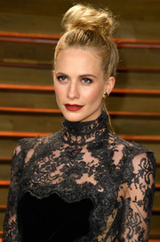 Poppy Delevingne looked fierce with her towering top knot at the Vanity Fair Oscar party.