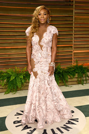 Serena Williams looked risque at the Vanity Fair Oscar party in a sheer-panel, floral mermaid gown by Michael Costello.