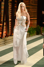 Lady Gaga made a grand entrance at the Vanity Fair Oscar party in a strapless white cutout gown by Atelier Versace.