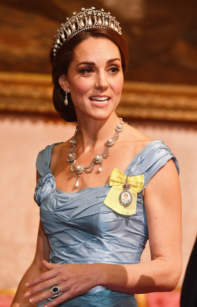 A yellow badge with an attached brooch featuring the Queen's portrait finished off Kate Middleton's look.