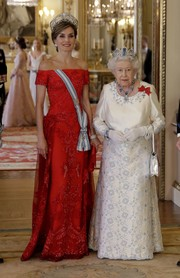 Queen Letizia of Spain was a vision in an embellished red off-the-shoulder gown by Felipe Varela while attending a State Banquet at Buckingham Palace.