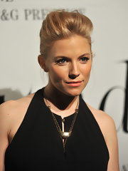 Sienna Miller styled her look with a crescent-shaped gold pendant.
