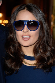 Salma Hayek accessorized with blue Stella McCartney shield sunglasses to match her dress.
