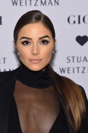 Olivia Culpo wore her long tresses in a neat side-parted ponytail during the launch of the Stuart Weitzman Gigi boot.
