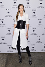 Gigi Hadid layered an unbuttoned white shirdress over a pair of jeans for the launch of the Stuart Weitzman Gigi boot.