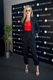 Georgia May Jagger sported an ultra-stylish black pantsuit with a red cowl-neck blouse at the Sunglass Hut cocktail party.