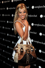 Mollie King flaunted her tan tote bag while attending the Sunglass Hut flagship store opening. While the bag may be cute it was a little big for her dainty white dress.