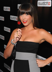 Erin holds a lollipop that matches her deep red lip color for the Swatch launch party.
