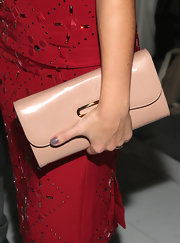 Minka Kelly balanced the vibrancy of her bright red dress with this nude leather clutch.
