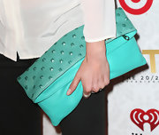 Nikki Reed added some color to her black and white look with this teal, fold-over clutch.