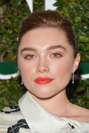 Florence Pugh perked up her beauty look with a swipe of bright orange lipstick.