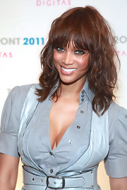 Tyra Banks styled her hair in carefree curls and wispy bangs while attending the 2011 New Front Conference.