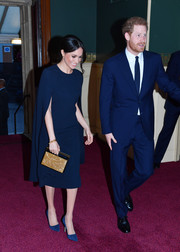 Meghan Markle styled her dress with a gold clutch by Naeem Khan.