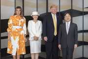 Melania Trump cut a bright figure in an orange and white print coat by Dries Van Noten while visiting Tokyo, Japan.