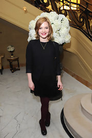 Holliday Grainger matched her black dress with a pair of plum tights.