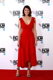 Gemma Arterton paired her lovely dress with black and gold ankle-strap sandals.