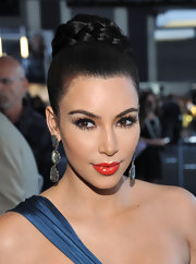 Kim Kardashian wore her hair in a braid-wrapped bun at the Theyskens' Theory Spring 2012 fashion show. Her hair was pulled up and a high ponytail was tightly secured. Then, her long tresses were twisted and pinned into place. The addition of a braided hair piece was then wrapped around the bun and secured.