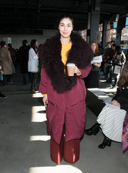 Caroline Issa kept cozy in a burgundy down coat with a fur collar during the Tibi fashion show.