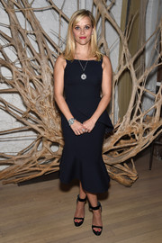 Reese Witherspoon cut a shapely silhouette in an asymmetrical navy peplum dress by Oscar de la Renta at the Tiffany & Co. 2015 Blue Book celebration.