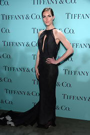 Hilary Rhoda chose an elegant gown that featured a ruffled train, a halter neckline, and a slit cutout on the bust for her red carpet look.