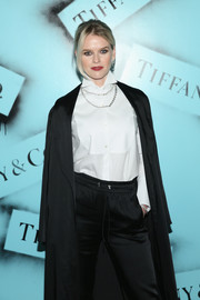 Alice Eve teamed a white tuxedo top with black trousers and a long coat for the Tiffany & Co. Modern Love photography exhibition.