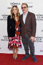 Underneath her jacket, Sarah Jessica Parker wore a red floral midi dress.