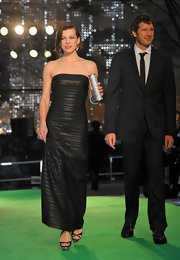 Milla Jovovich paired her elegant black evening gown with strappy sandals complete with a silver glittering platform.