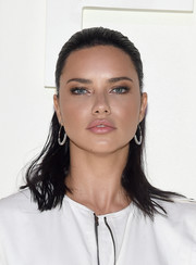 Adriana Lima sported a slick half-up hairstyle at the Tom Ford Spring 2019 show.