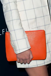 Olivia Munn added some cheerful color to her look with an orange zip clutch.