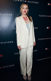 Dakota Johnson made her all-white pantsuit pop with a bright red statement necklace and red lips.