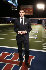 Johannes Huebl cut a dashing profile in a black Tommy Hilfiger suit during the label's fashion show.