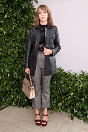 Maya Hawke layered a black leather jacket over a sheer blouse for the Tory Burch Spring 2020 show.