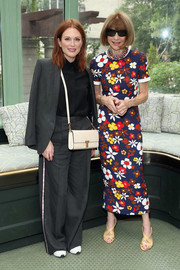 Anna Wintour donned a colorful floral frock and her signature strappy heels for the Tory Burch Spring 2019 show.