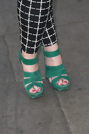 Alexandra Roach added some color to her black and white ensemble by sporting these strappy green sandals.