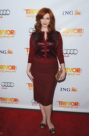 Christina Hendricks look festive in a sparkly maroon sequined cardigan and a matching pencil skirt.