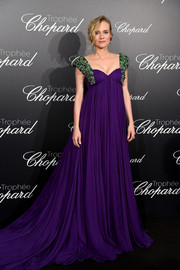 Diane Kruger looked splendid in a purple Prada empire gown with bejeweled shoulders at the Trophee Chopard photocall during Cannes.