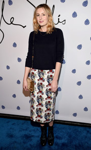 A tan velvet bag with a gold chain strap finished off Laura Carmichael's ensemble.