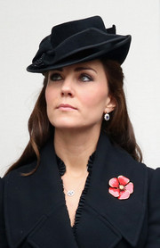 Kate Middleton attended a military event wearing an Alexander McQueen flared wool coat, a decorative Jane Corbett hat, and a lovely red poppy pin.
