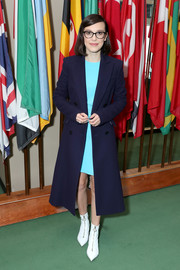 Millie Bobby Brown layered a navy Calvin Klein coat over an aqua mini dress for the UNICEF World Children's Day event.