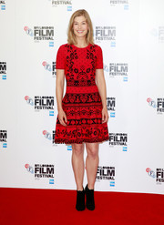 Rosamund Pike looked festive in a red and black floral fit-and-flare dress at the BFI London Film Festival photocall for 'A United Kingdom.'