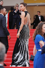 Irina Shayk attended the Cannes premiere of 'The Unknown Girl' wearing a black Miu Miu gown that was simple from the front but absolutely gorgeous from behind with its crystal and feather embellishments!